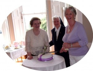 The three McTigue sisters join together in the cutting of the Jubilee cake at the reception in the dining-room Magheramore
